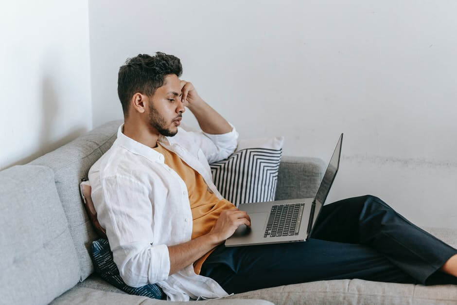 A man using a laptop computer sitting on top of a bed